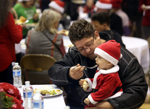 Mario Solano, left, feeds his son, Mario Solano, Jr. during the Community Holiday Dinner, at the Community Church of Sebastopol, Calif. on Tuesday, Dec. 25, 2012.  The holiday event, which is sponsored by the Rotary Club of Sebastopol Sunrise, provides food, clothes and toys for the needy. (AP Photo/The Press Democrat, Christopher Chung)