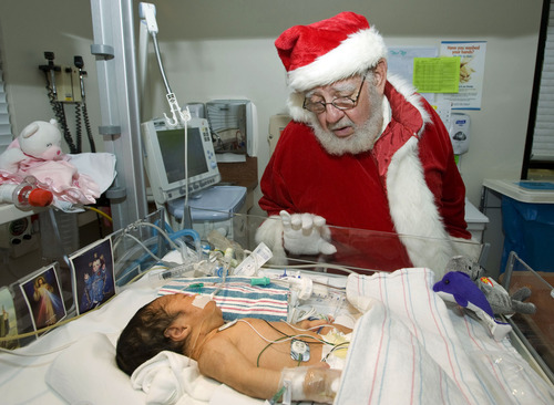 "In this Monday, Dec. 24, 2012 photo, Santa Claus whispers ""get well wishes"" to newborn baby girl Dalayna Molina, who is recovering from pneumonia, in the intensive care unit at Fountain Valley Hospital in Fountain Valley, Calif. (AP Photo/The Orange County Register,  Rose Palmisano)   MAGS OUT; LOS ANGELES TIMES OUT"