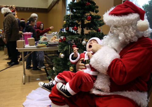 Mario Solano, Jr. cries on Santa's lap as his father tries to take a picture during the Community Holiday Dinner, at the Community Church of Sebastopol, Calif. on Tuesday, Dec. 25, 2012.  The holiday event, which is sponsored by the Rotary Club of Sebastopol Sunrise, provides food, clothes and toys for the needy. (AP Photo/The Press Democrat, Christopher Chung)
