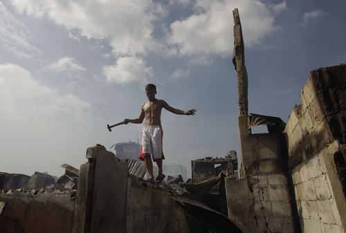 A Filipino resident balances on a wall as he salvages items after a fire hit a slum area in suburban San Juan, east of Manila, Philippines on Christmas day Tuesday Dec. 25, 2012. Fire Officer 2 Noel Binwag said about 2,000 families were left homeless during the fire. Six people also died when a row of apartments went up in flames in a separate fire in suburan Quezon city. (AP Photo/Aaron Favila)