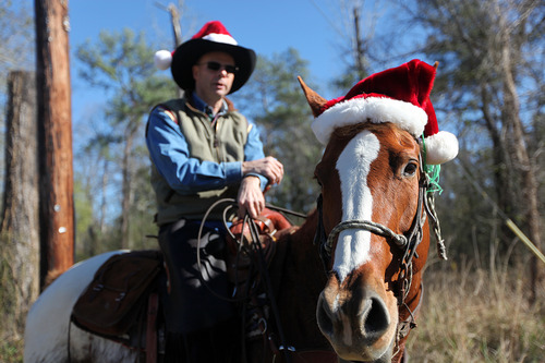 Dion Bandenbosch and his horse. Fire in the Wind, both wear Santa hats as they take a Christmas Day ride along FM 1486 on Tuesday, Dec. 25, 2012, near Montgomery, Texas.   (AP Photo/Houston Chronicle, Mayra Beltran) MANDATORY CREDIT
