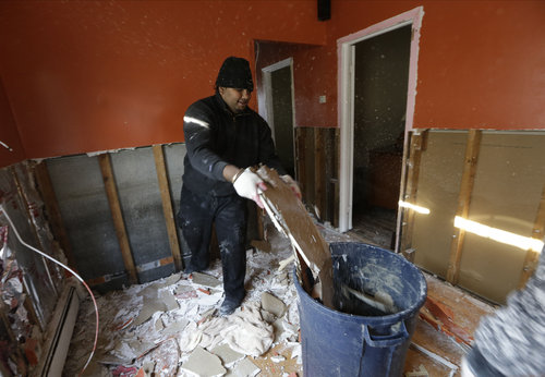 Fork lift driver Mohabir Tejnarine, who works at nearby John F. Kennedy airport, discards sheetrock after pulling it from the walls of his home on Christmas Day in the Rockaways section of New York, Tuesday, Dec. 25, 2012.  Tejnarine's bungalow style home, which borders Jamaica Bay, was flooded by storm surge from Superstorm Sandy nearly two months ago. Tejnarine enlisted family members to help with the wall-removal job, required before mold-removal specialists can rid mildew from the once-flooded house.  (AP Photo/Kathy Willens)