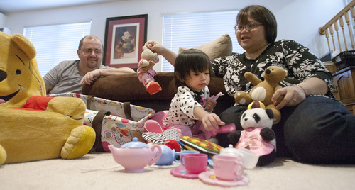 Steve Griffin   The Salt Lake Tribune  Miriam Jensen, 20-months, plays with her parents, Farah and Jhan Jensen, in their Roy home Monday December 24, 2012. They have been trying to adopt Miriam from Malaysia since she was born. But through a pile of red tape and difficulties, they've never been able to bring her back to Utah. Until now. She arrived last week and will spend Christmas with her parents. According to the State Department, there have only been 16 successful adoptions from Malaysia between 1999 and 2011.