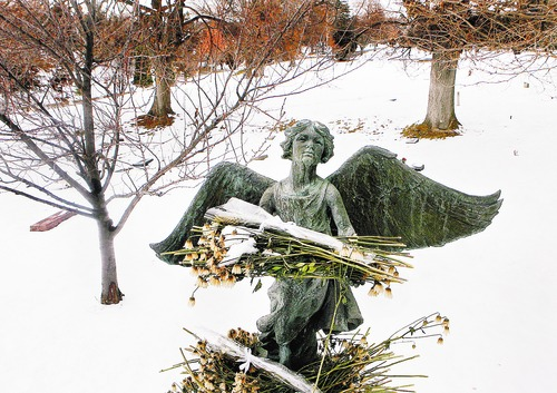 "Scott Sommerdorf  |  Salt Lake Tribune ANGELS IN SLC The ""Christmas Box Angel"" in the Salt Lake Cemetery. Visitors to the cemetery have adorned the angel with flowers that have since wilted."