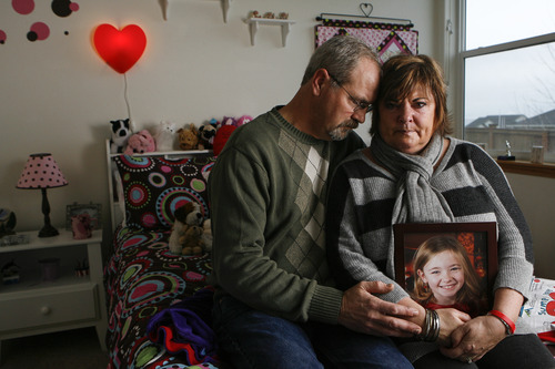 In this Saturday, Dec. 22, 2012 photo, Paul and Judy Neiman hold a photo of their daughter, Sydnee, in her bedroom at their home in West Richland, Wash. Sydnee died in late 2011 after Judy accidentally backed over her with her SUV. Although there is a law in place that calls for new manufacturing requirements to improve the visibility behind passenger vehicles, the standards have yet to be mandated because of delays by the U.S. Department of Transportation. (AP Photo/Kai-Huei Yau)