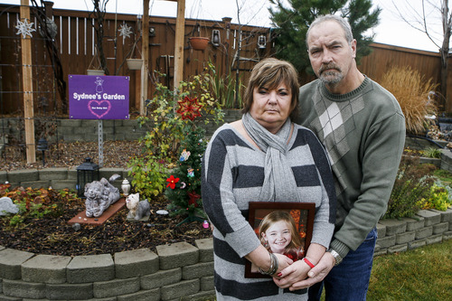 In this Saturday, Dec. 22, 2012 photo, Judy and Paul Neiman pose for a photo as she holds a photo of their daughter, Sydnee, next to a garden dedicated to her in West Richland, Wash. Sydnee died in late 2011 after Judy accidentally backed over her with her SUV. Although there is a law in place that calls for new manufacturing requirements to improve the visibility behind passenger vehicles, the standards have yet to be mandated because of delays by the U.S. Department of Transportation. (AP Photo/Kai-Huei Yau)