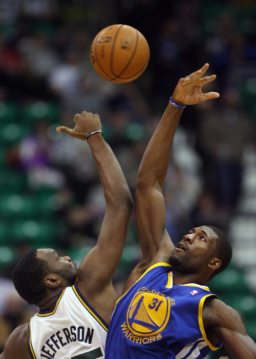 Steve Griffin | The Salt Lake Tribune   Utah's Al Jefferson and Golden State's Festus Ezeli battle for the opening tip during first half action of the Utah Jazz Versus Golden State Warriors game at EnergySolutions Arena in Salt Lake City, Utah Wednesday December 26, 2012.