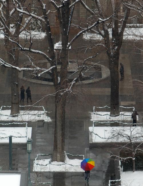 Trent Nelson  |  The Salt Lake Tribune People walking through a wet Temple Square Wednesday December 26, 2012 in Salt Lake City.