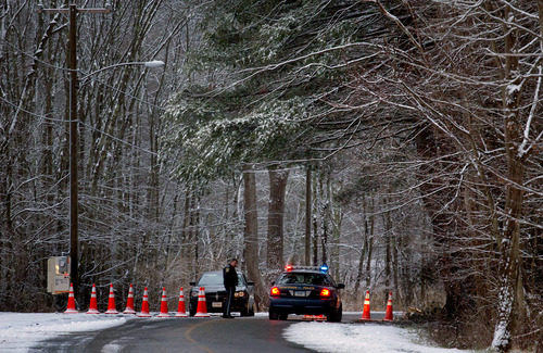 Police continue to block the road to Sandy Hook Elementary School in Newtown, Conn. Tuesday, Dec. 25, 2012.   On Tuesday police officers from elsewhere are on duty, to give local officers a break on Christmas.  (AP Photo/Craig Ruttle)