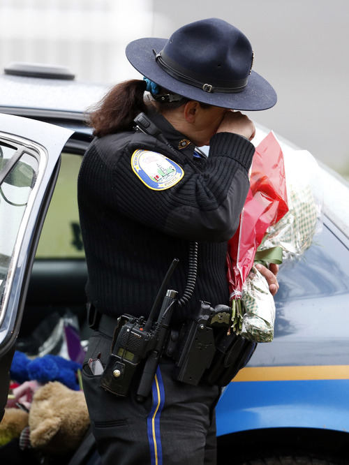 Newtown Police Officer Maryhelen McCarthy wipes away tears while placing flowers at a makeshift memorial outside of St. Rose of Lima Roman Catholic Church, Sunday, Dec. 16, 2012, in Newtown, Conn. On Friday, a gunman allegedly killed his mother at their home and then opened fire inside the Sandy Hook Elementary School, killing 26 people, including 20 children. (AP Photo/Julio Cortez)