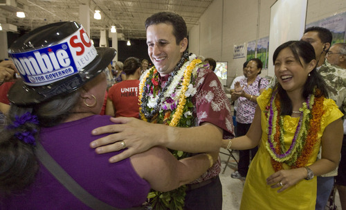 FILE- In this Nov. 3, 2010 file photo, a supporter congratulates then-Lt. governor-elect Brian Schatz, center, as his wife Linda looks on at the Neil Abercrombie-Brian Schatz Hawaii governor's post election party in Honolulu. Schatz was appointed by Gov. Neil Abercrombie Wednesday, Dec. 26, 2012 to succeed the late U.S. Sen. Daniel Inouye. (AP Photo/Eugene Tanner, File)