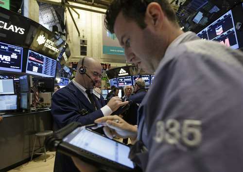 Floor traders check their handheld computers at the New York Stock Exchange in New York, Wednesday, Dec. 26, 2012.  (AP Photo/Kathy Willens)