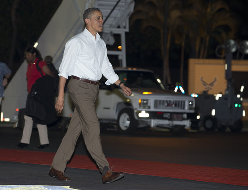 President Barack Obama walks across the tarmac to board Air Force One at Honolulu Joint Base Pearl Harbor-Hickam, Wednesday, Dec. 26, 2012, in Honolulu, en route to Washington. With a yearend deadline looming before the economy goes off the so called fiscal cliff, the president is cutting short his traditional Christmas holiday in Hawaii. (AP Photo/Carolyn Kaster)