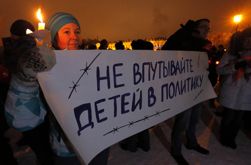 "Opposition activists hold a poster reading ""Do not involve children in politics"" during a protest against a bill banning U.S. adoptions of Russian children in St. Petersburg, Russia, Wednesday, Dec. 26, 2012. Defying a storm of domestic and international criticism, Russia moved toward finalizing a ban on Americans adopting Russian children, as Parliament's upper house voted unanimously Wednesday in favor of a measure that President Vladimir Putin has indicated he will sign into law. (AP Photo/Dmitry Lovetsky)"
