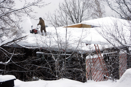 Francisco Kjolseth  |  The Salt Lake Tribune If work is to continue sometimes you need to run the snow blower on the roof as a construction worker tries to clear the snow from the most recent storm on a new home build in the Olympus Cove neighborhood on Thursday.