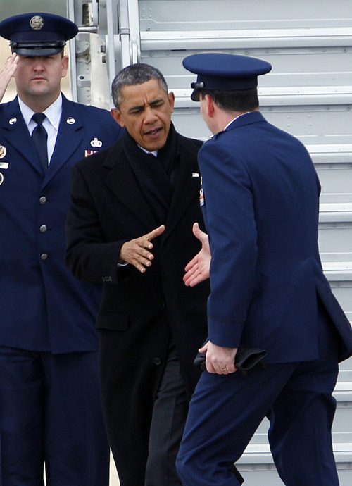 "President Barack Obama is greeted by Col. Greg N. Urtso, Vice Commander of the 11th Wing, after deplaning from Air Force One upon his arrival at Andrews Air Force Base, Md., Thursday, Dec. 27,  2012. The president cut short his holiday and returned to Washington as no deal appeared in sight to avoid the year-end ""fiscal cliff"" of higher taxes and deep spending cuts that could spin the still-fragile back into a recession. The treasury secretary warned that the government would hit its borrowing limit on Monday, the final day of the year.  (AP Photo/Jose Luis Magana)"