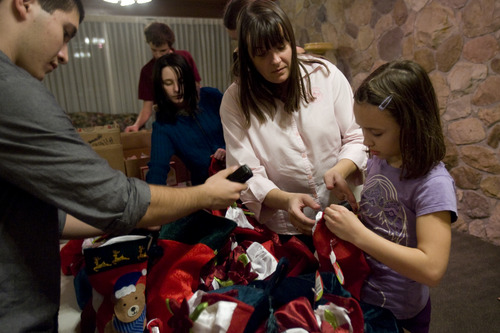 Kim Raff  |  The Salt Lake Tribune Chrystal Butterfield helps Breann Burningham stuffs stockings for soldiers with her son (left) Chad Butterfield during a volunteer work day for the Stockings for Soldiers program at Redwood Cemetery in Taylorsville on November 29, 2012. Butterfield is a very active volunteer, on top of working full-time and raising three kids.