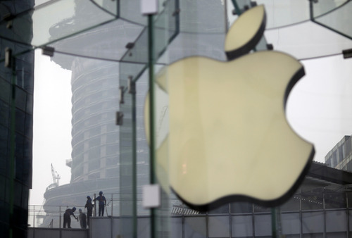 FILE - In this Friday, July 20, 2012 file photo, workers clean the rooftop of a building near an Apple Store in Shanghai, China. Apple was one of the star performers of the first quarter of 2012 and was probably the year's most talked-about company. The popularity of the iPhone and iPad led to staggering sales growth that helped push its stock up 48 percent to almost $600 at the end of March. Apple also announced a dividend and overtook Exxon Mobil as the United States' most valuable company. Investor optimism faded though and prompted a sell-off. (AP Photo/Eugene Hoshiko, File)