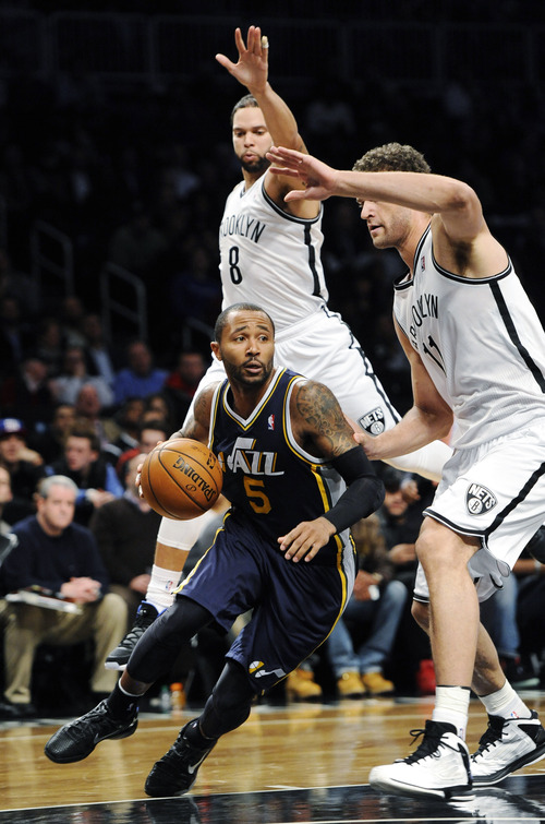 Utah Jazz's Mo Williams (5) drives the ball around Brooklyn Nets' Deron Williams (8) and Brook Lopez (11) in the first half of an NBA basketball game, Tuesday, Dec., 18, 2012, at Barclays Center in New York. The Jazz won 92-90. (AP Photo/Kathy Kmonicek)
