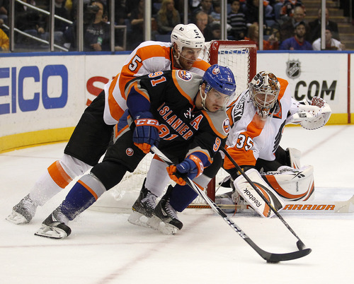 New York Islanders' John Tavares (91) is covered by Philadelphia Flyers' Braydon Coburn (5) while circling the net while Flyers goaltender Sergei Bobrovsky (35) defends the goal during the second period of an NHL hockey game at Nassau Coliseum in Uniondale, N.Y., Wednesday, Nov. 23, 2011. The Flyers won 4-3 in overtime.  (AP Photo/Paul J. Bereswill)