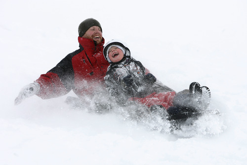 Rick Egan  | The Salt Lake Tribune   Brent Giles (left) and Dylan Giles enjoy the new snow as they sled on a hill near Mueller Park Jr. High in Bountiful on Friday, Dec. 28, 2012.