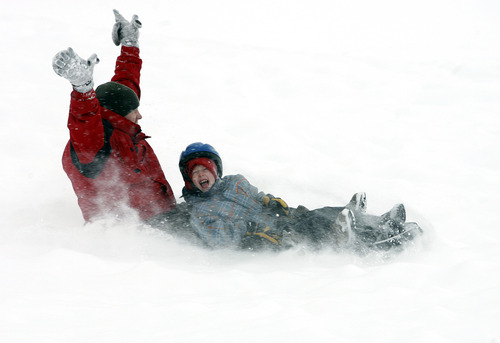 Rick Egan  | The Salt Lake Tribune   Brent Giles (left) and Brandon Giles enjoy the new snow as they sled on a hill near Mueller Park Jr. High in Bountiful on Friday, Dec. 28, 2012.