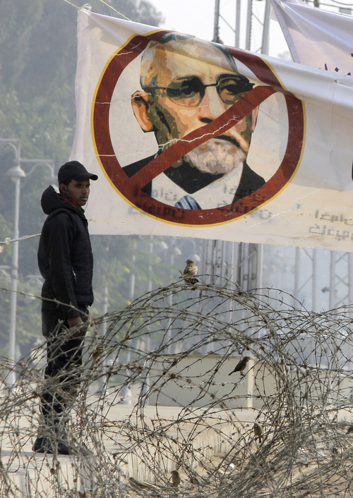 An Egyptian anti-riot soldier stands under a banner showing Muslim Brotherhood leader Mohammed Badie and barbed wire near the presidential palace in Cairo, Egypt, Friday, Dec. 28, 2012. The official approval of Egypt's disputed, Islamist-backed constitution held out little hope of stabilizing the country after two years of turmoil and Islamist President Mohammed Morsi may now face a more immediate crisis with the economy falling deeper into distress. (AP Photo/Amr Nabil)