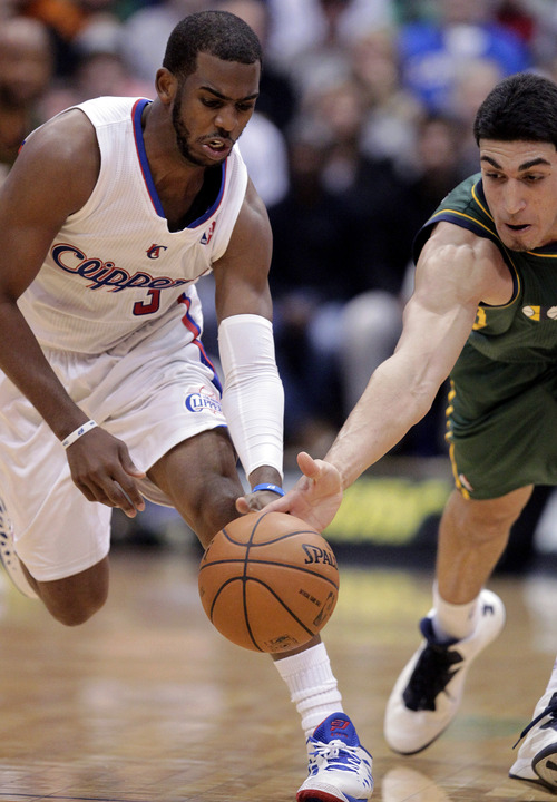 Los Angeles Clippers point guard Chris Paul, left, and Utah Jazz center Enes Kanter (0) battle for a loose ball in the second half of an NBA basketball game Friday, Dec. 28, 2012, in Salt Lake City. The Clippers defeated the Jazz 116-114. (AP Photo/Rick Bowmer)