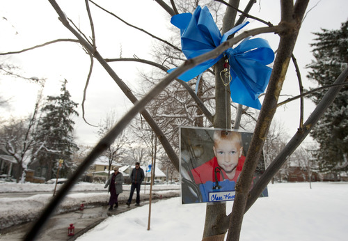 Steve Griffin |  The Salt Lake Tribune A photograph of 7-year-old Chase Kowalski, one of the 20 children murdered in Newtown, Conn., Dec. 14, hangs from a tree as people walk through a new grove of eastern redbud trees Thursday at the entrance to the Salt Lake City Cemetery. The grove was dedicated by Salt Lake City officials and other community leaders in remembrance of the victims of the Newtown shootings at a ceremony at the entrance to the cemetery on Thursday. Salt Lake City Urban Forester Bill Rutherford planned the memorial.