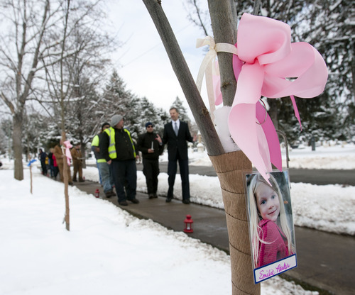 Steve Griffin | The Salt Lake Tribune A photograph of 6-year-old Emilie Parker, one of the 20 children murdered in Newtown, Conn., Dec. 14, hangs from a tree as people walk through a new grove of eastern redbud trees Thursday at the entrance to the Salt Lake City Cemetery. The grove was dedicated by Salt Lake City officials and other community leaders in remembrance of the victims of the Newtown shootings at a ceremony at the cemetery Thursday December 27, 2012. Salt Lake City Urban Forester Bill Rutherford planned the memorial. Emilie was buried in Ogden last week.