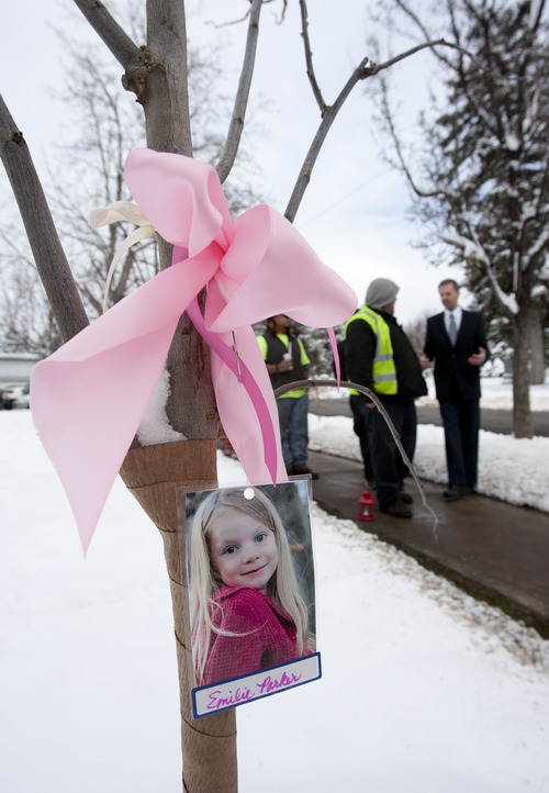 Steve Griffin |  The Salt Lake Tribune A photograph of 6-year-old Utah native Emilie Parker hangs from a tree as people walk through a new grove of eastern redbud trees that was dedicated by Salt Lake City officials and other community leaders in remembrance of the victims of the Newtown, Conn., shootings at a ceremony at the entrance to the Salt Lake City Cemetery Thursday December 27, 2012. Emilie was one of 20 children killed in the rampage.