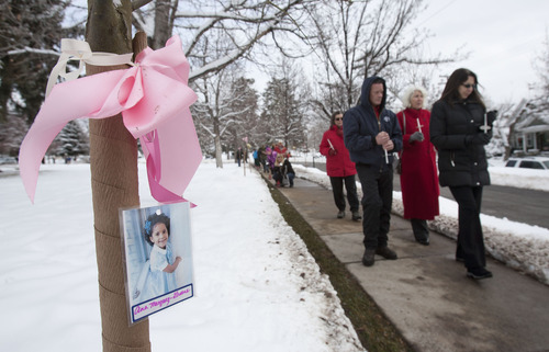 Steve Griffin  |  The Salt Lake Tribune A photograph of 6-year-old Ana Marquez-Greene, one of the 20 children murdered in Newtown, Conn., Dec. 14, hangs from a tree as people walk through a new grove of eastern redbud trees Thursday at the entrance to the Salt Lake City Cemetery. The grove was dedicated by Salt Lake City officials and other community leaders in remembrance of the victims of the Newtown shootings at a ceremony at the cemetery on Thursday December. Salt Lake City Urban Forester Bill Rutherford planned the memorial.
