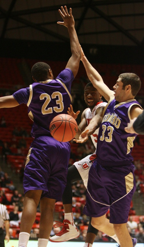 Kim Raff  |  The Salt Lake Tribune University of Utah guard Jarred DuBois (5) shoots through College of Idaho players (left) Antonio Garrett and Taylor Pruett at the Huntsman Center in Salt Lake City on December 28, 2012.