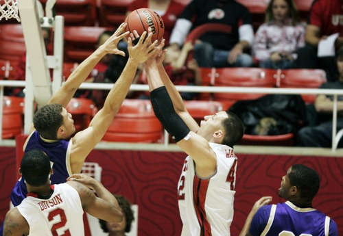 Kim Raff  |  The Salt Lake Tribune University of Utah center Jason Washburn (42) competes with College of Idaho player Sydney Donaldson for a rebound during a game at the Huntsman Center in Salt Lake City on December 28, 2012.