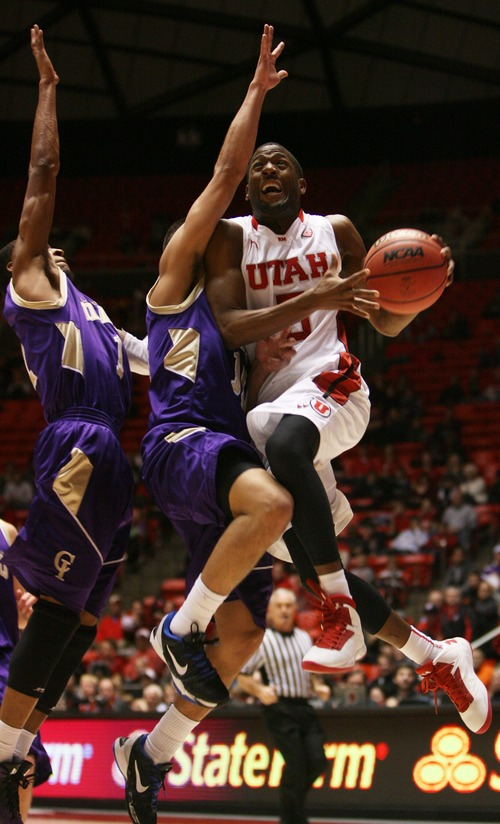 Kim Raff  |  The Salt Lake Tribune University of Utah guard Jarred DuBois (5) shoots the ball as College of Idaho players (left) Rodney Delgardo and (middle) Miguel Rodriguez defend during a game at the Huntsman Center in Salt Lake City on December 28, 2012.
