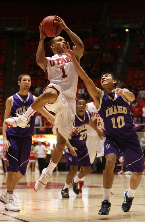 Kim Raff  |  The Salt Lake Tribune (left) University of Utah guard Glen Dean (1) shoots the ball as College of Idaho player Miguel Rodriguez defends during a game at the Huntsman Center in Salt Lake City on December 28, 2012.