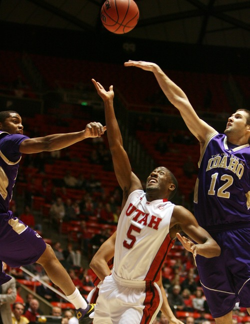Kim Raff  |  The Salt Lake Tribune University of Utah guard Jarred DuBois (5) shoots the ball as College of Idaho players (left) Antonio Garrett and (right) Duncan Koga defend during a game at the Huntsman Center in Salt Lake City on December 28, 2012.