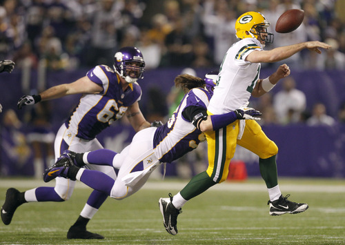 Green Bay Packers quarterback Aaron Rodgers, right, fumbles the ball as he is hit by Minnesota Vikings defensive end Brian Robison during the second half of an NFL football game Sunday, Dec. 30, 2012, in Minneapolis. (AP Photo/Genevieve Ross)