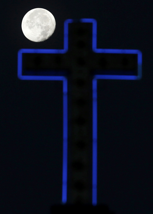 The moon is seen in its waning gibbous stage over the glowing neon outline of a cross on top of the Maria Magdalena de Tepexpan Catholic Church, Sunday, Dec. 30, 2012 in Tepexpan, Mexico. The church, which is in a small town north east of Mexico City, was built in 1542. (AP Photo/Julio Cortez)