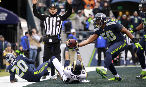 St. Louis Rams' Austin Pettis (18) scores a touchdown as Seattle Seahawks' K.J. Wright (50) and Jeremy Lane (20) look on in the first half of an NFL football game, Sunday, Dec. 30, 2012, in Seattle. (AP Photo/Stephen Brashear)