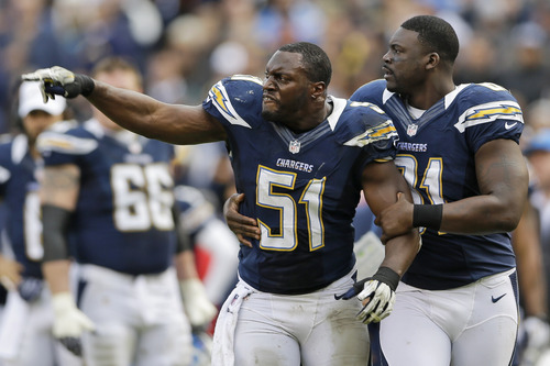 San Diego Chargers inside linebacker Takeo Spikes (51) yells as he is held back by tight end Randy McMichael after Spikes was ejected from the NFL football game along with Oakland Raiders running back Mike Goodson, during the first half Sunday, Dec. 30, 2012, in San Diego. (AP Photo/Lenny Ignelzi)