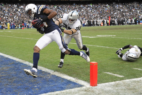 San Diego Chargers wide receiver Danario Alexander, left, runs the ball into the end zone for a touchdown as Oakland Raiders free safety Matt Giordano (27) tries to push him out of bounds during the second half of an NFL football game Sunday, Dec. 30, 2012, in San Diego. (AP Photo/Denis Poroy)