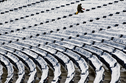 A worker spreads salt to melt ice and clear snow from the stands at Ralph Wilson Stadium before an NFL football game between the New York Jets and Buffalo Bills, Sunday, Dec. 30, 2012, in Orchard Park, N.Y. (AP Photo/Mel Evans)