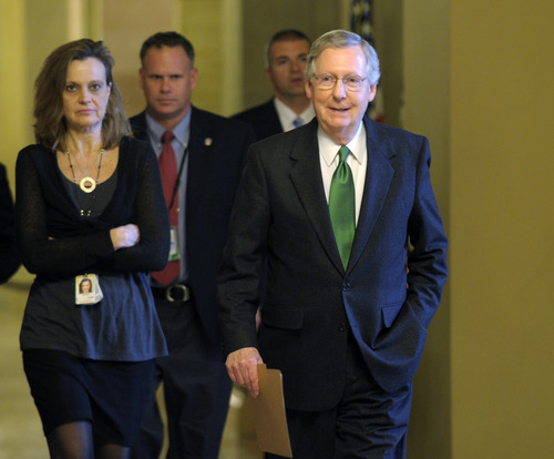 """Senate Minority Leader Mitch McConnell of Ky. walks toward the Senate floor on Capitol Hill in Washington, Monday, Dec. 31, 2012. McConnell said Monday that he and the White House have agreed on preventing tax hikes that the """"fiscal cliff"""" will trigger after midnight. And he says they are very close to an overall deal that would also prevent budget-wide spending cuts.  (AP Photo/Susan Walsh)"""