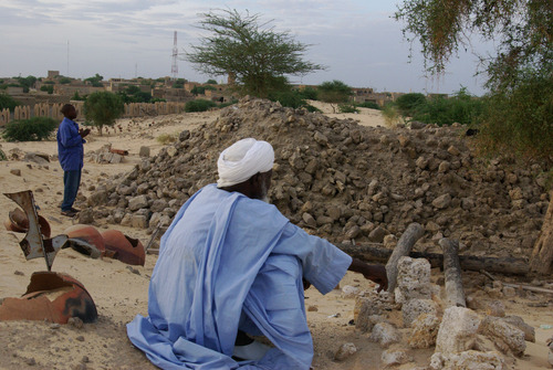 In this Oct. 19, 2012 photo, men pray beside the tombs of locally venerated Islamic saints, whose mausoleums were destroyed by Islamist group Ansar Dine, in Timbuktu, Mali. In recent months, al-Qaida and its allies have taken advantage of political instability within Mali to push out of their hiding place and into the towns, taking over an enormous territory which they are using to stock arms, train forces and prepare for global jihad. And as 2012 draws to a close and the world hesitates, delaying a military intervention, the extremists who seized control of the area earlier this year are preparing for a war they boast will be worse than the decade-old struggle in Afghanistan. (AP Photo)
