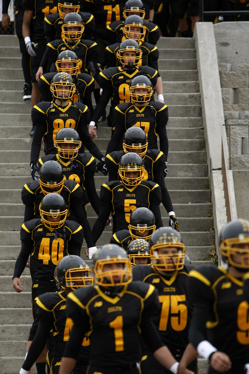 Tribune file photo The Cottonwood High football team in 2009 walks onto the field that Scott Cate's donations paid for.