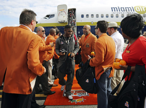 Northern Illinois players are greeted by Orange Bowl Committee Members handing out oranges and gift bags as the team arrives at Miami International Airport, Wednesday, Dec. 26, 2012, in Miami. Northern Illinois is scheduled to play Florida State in the Orange Bowl NCAA college football game on Tuesday, Jan. 1, 2013. (AP Photo/The Miami Herald, Emily Michot)  MAGS OUT