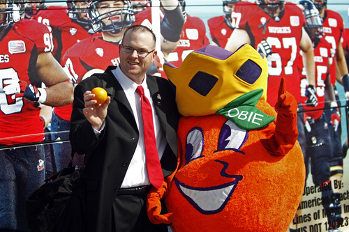 Northern Illinois head coach Rod Carey poses for photos with Obie, the Orange Bowl mascot, as the team arrives at Miami International Airport, Wednesday, Dec. 26, 2012, in Miami. Northern Illinois is scheduled to play Florida State in the Orange Bowl NCAA college football game on Tuesday, Jan. 1, 2013. (AP Photo/The Miami Herald, Emily Michot)  MAGS OUT