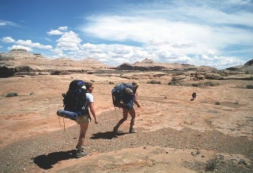 Al Hartmann  |  The Salt Lake Tribune Hikers make their way across slickrock to the Dirty Devil River.