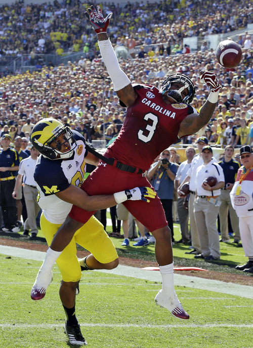 South Carolina cornerback Akeem Auguste (3) breaks up a pass intended for Michigan wide receiver Joe Reynolds (85) during the first quarter of the Outback Bowl NCAA college football game, Tuesday, Jan. 1, 2013, in Tampa, Fla. (AP Photo/Chris O'Meara)